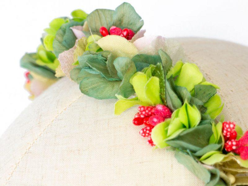 Diadema de flores verde y roja para invitada